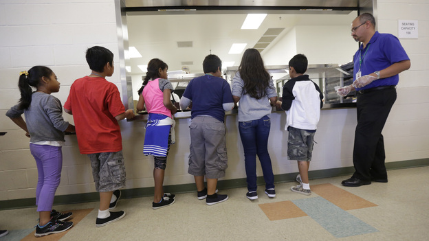 Detained immigrant children line up in the cafeteria at the Karnes County Residential Center, in Karnes City, Texas, a temporary home for immigrant women and children detained at the border. (AP)