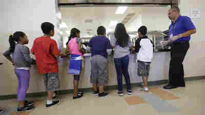 Young immigrants line up in the cafeteria at the Karnes County Residential Center, in Karnes City, Texas, a temporary home for immigrant women and children detained at the border.