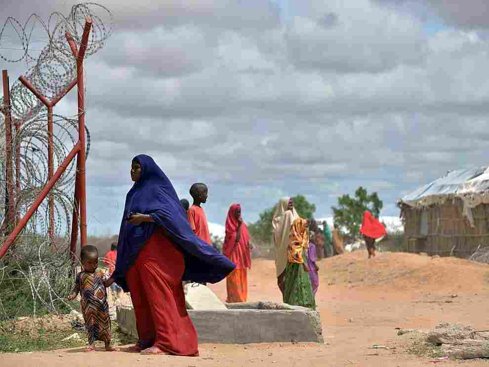 A refugee stands with her son just outside a fenced perimeter at the sprawling Dadaab refugee camp in May 2015.