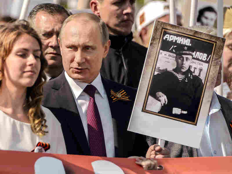 Russian president Vladimir Putin holds a portrait of his father who fought in World War II during today's Moscow parade marking Victory Day in Russia.