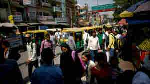 Cars, motorcycles, and rickshaws all share the crowded streets of New Delhi.