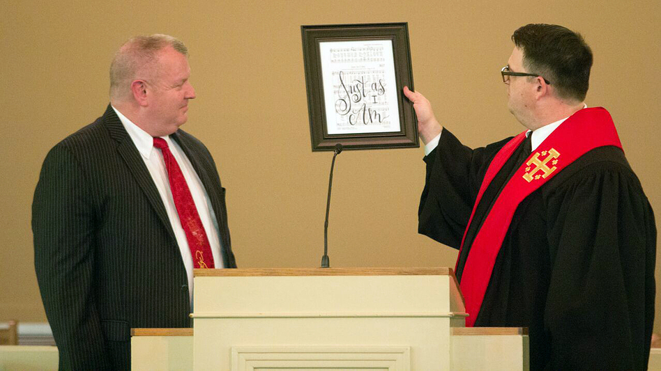 """Nick Wilson (left), at his ordination last month, is given a framed sign from Pastor Matt Johnson that reads """"Just As I Am,"""" the title of one of Wilson's favorite hymns. (Bill Campbell)"""