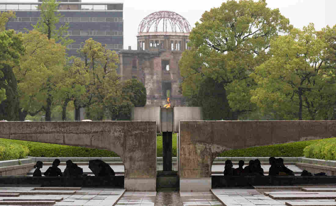 Visitors shelter from the rain under the Peace Flame as they visit the Memorial Park and the nearby Hiroshima Peace Memorial Museum on April 21 in Hiroshima, Japan. The dome in the background was destroyed during the attack, and preserved as a monument The park, museum and dome are dedicated to the victims of the world's first nuclear attack, and to the pursuit of peace.