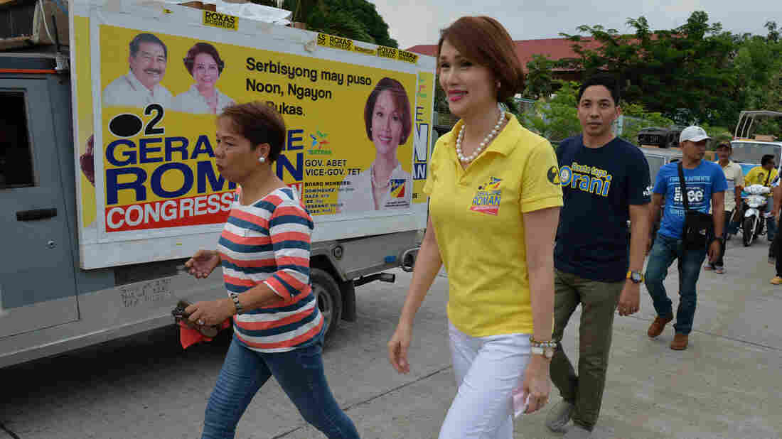 Geraldine Roman walks past a campaign poster during an April 30 trip to the town of Orani, in the province of Bataan, north of Manila. The 49-year-old, a member of a powerful political family, has won a seat in the nation's lower house, according to unofficial results.
