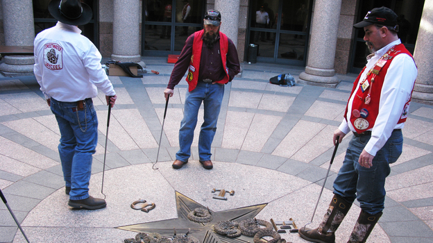 Sweetwater Jaycees surrounding rattlesnakes on Diamondback Day at the Texas state Capitol. (NPR)