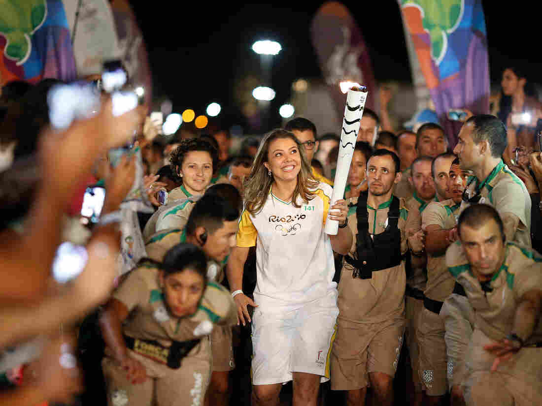 The Olympic flame gets a lift from former Brazilian volleyball player Leila Barros, who took part in this month's torch relay. The games are set to begin on August 5.