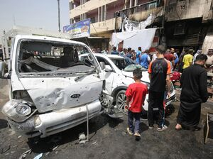 Iraqis look at the damage following a car bomb attack in Sadr City, a Shiite area north of the capital, Baghdad, on Wednesday.