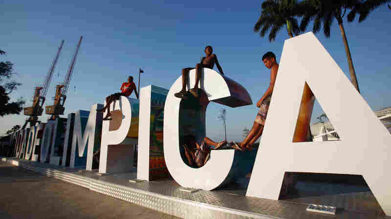 "Teenagers sit on a new sign reading ""Cidade Olimpica"" (Olympic City) in Rio de Janeiro's port district last October. Ahead of this summer's Olympic Games, the port district is undergoing an urban renewal program. Ticket sales have been slow, and many Brazilians cite the poor state of the economy, which is in recession."