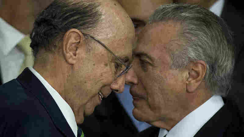Brazil's new finance minister Henrique Meirelles (left) and acting President Michel Temer gesture during the Cabinet inauguration ceremony in Brazil's capital Brasilia, on Thursday. Brazilian President Dilma Rousseff was suspended earlier to face an impeachment trial.