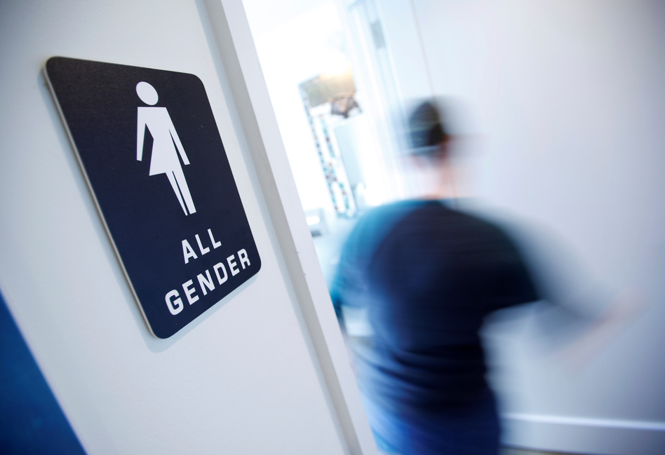 A bathroom sign welcomes both genders at the Cacao Cinnamon coffee shop in Durham, N.C., on May 3. (Jonathan Drake/Reuters)
