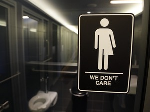 North Carolina is in a legal battle over a state law that requires transgender people to use the public restroom matching the sex on their birth certificate. The ADA-compliant bathroom signs were designed by artist Peregrine Honig.