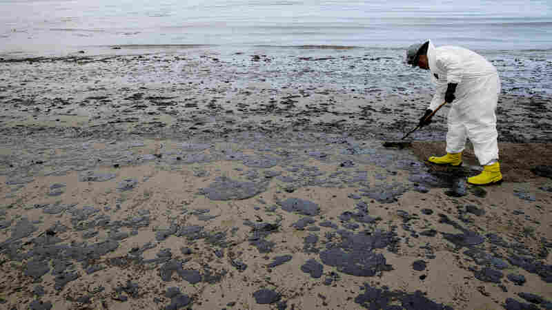A worker removes oil at California's Refugio State Beach on May 21, 2015.