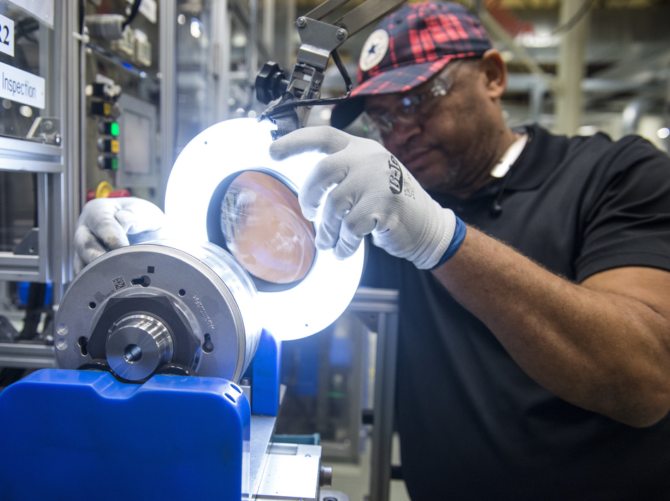 An employee inspects a component for hybrid electric vehicle motors at the Toshiba International Corp. manufacturing facility in Houston. (Bloomberg/Bloomberg via Getty Images)