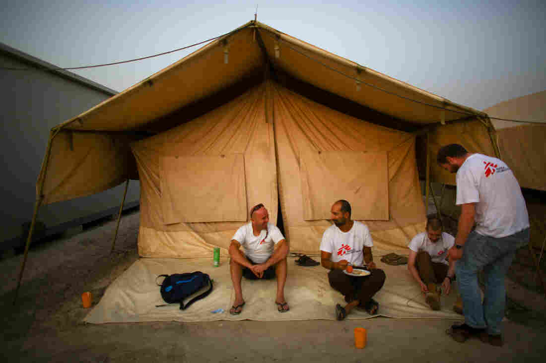 Dr. Nav, finishing up his breakfast, chats with some of his MSF colleagues. The foreign staff live two to a tent.