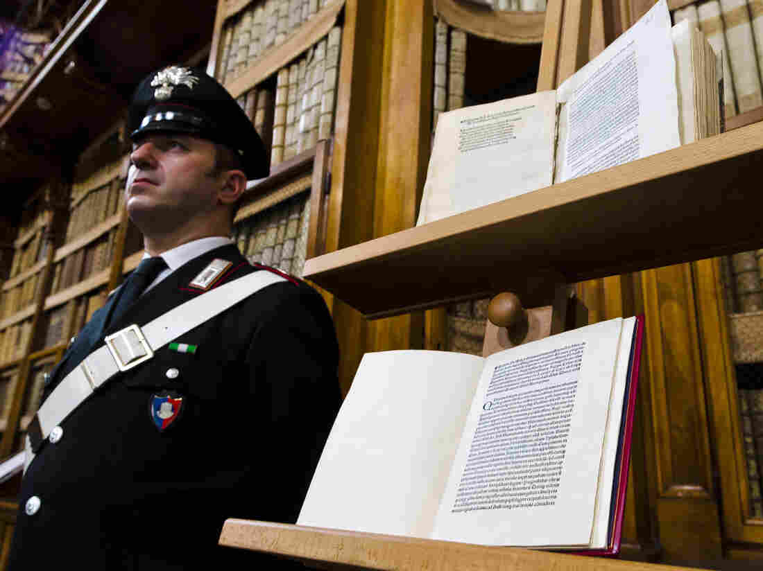 A Carabinieri policeman stands next to a book (bottom) reproducing a letter written by Christopher Columbus in 1493 about his discovery of the New World that had been replaced at Florence's Riccardiana library with a forgery (top) that no one noticed until a few years ago, during a press conference in Rome.