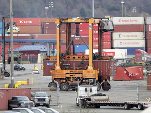 Ships transporting containers like these at the Port of Tacoma, Washington, last year carry the goods at issue in the TPP deal. A new report says the trade pact would boost the U.S. economy, but only by a modest amount.