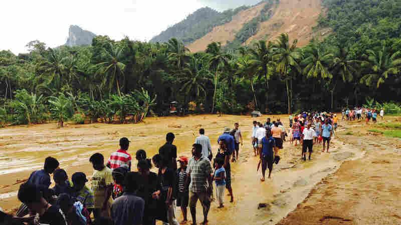 Sri Lankans slogged through the mud after massive landslides crashed down onto three villages in central Sri Lanka.
