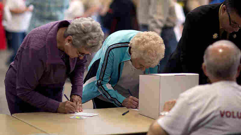 Two women cast their ballots for Republican candidates during the state's Republican caucuses on March 5 in Wichita, Kan.