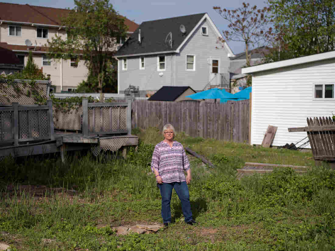 Like many other homeowners, Ann Marie Cianci — standing near her abandoned house on Staten Island, N.Y. — has been unable to move back home. After paying flood insurance for 32 years, she only received $60,000 out of her $250,000 policy.