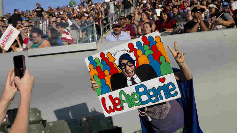 Brooke Peterson poses for photos with a sign at a rally for Democratic presidential candidate Sen. Bernie Sanders, I-Vt., on Tuesday in Carson, Calif.