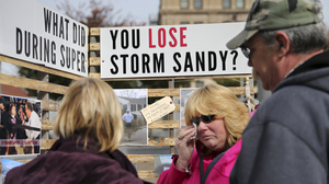 Sue Kenneally, center, wipes tears as she and other victims of Superstorm Sandy gather during a demonstration across from the statehouse in Trenton, N.J., in October, 2015. More than three years after the 2012 storm, many residents are still not back in their homes.