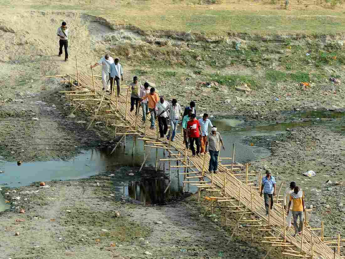 People cross a temporary bridge on a parched area of the Ganges River in Allahabad, India, on Thursday.