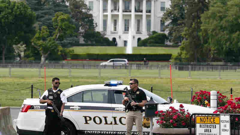 Law enforcement personnel stand south of the White House on Constitution Ave., in Washington, D.C., on Friday,. The White House was placed on a security alert after a Secret Service officer shot a man brandishing a firearm near a security checkpoint on a street outside the White House.