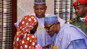 Nigerian president Muhammadu Buhari speaks with freed Chibok schoolgirl Amina Ali Nkeki, who is carrying her baby, as Borno state governor Kashim Shettima (C) looks on in Abuja, on May 19, 2016.