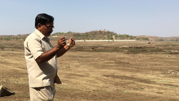 Ambadas Raut uses copper rods known as dowsing sticks to locate sources of underground water in a dry reservoir. He's had 400 clients and says he's found water for 80 percent of them. (NPR)