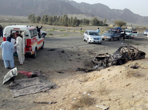 Volunteers stand Saturday near the wreckage of the destroyed vehicle, in which Mullah Akhtar Mansour was allegedly traveling in the Ahmed Wal area in Baluchistan province of Pakistan, near Afghanistan border.