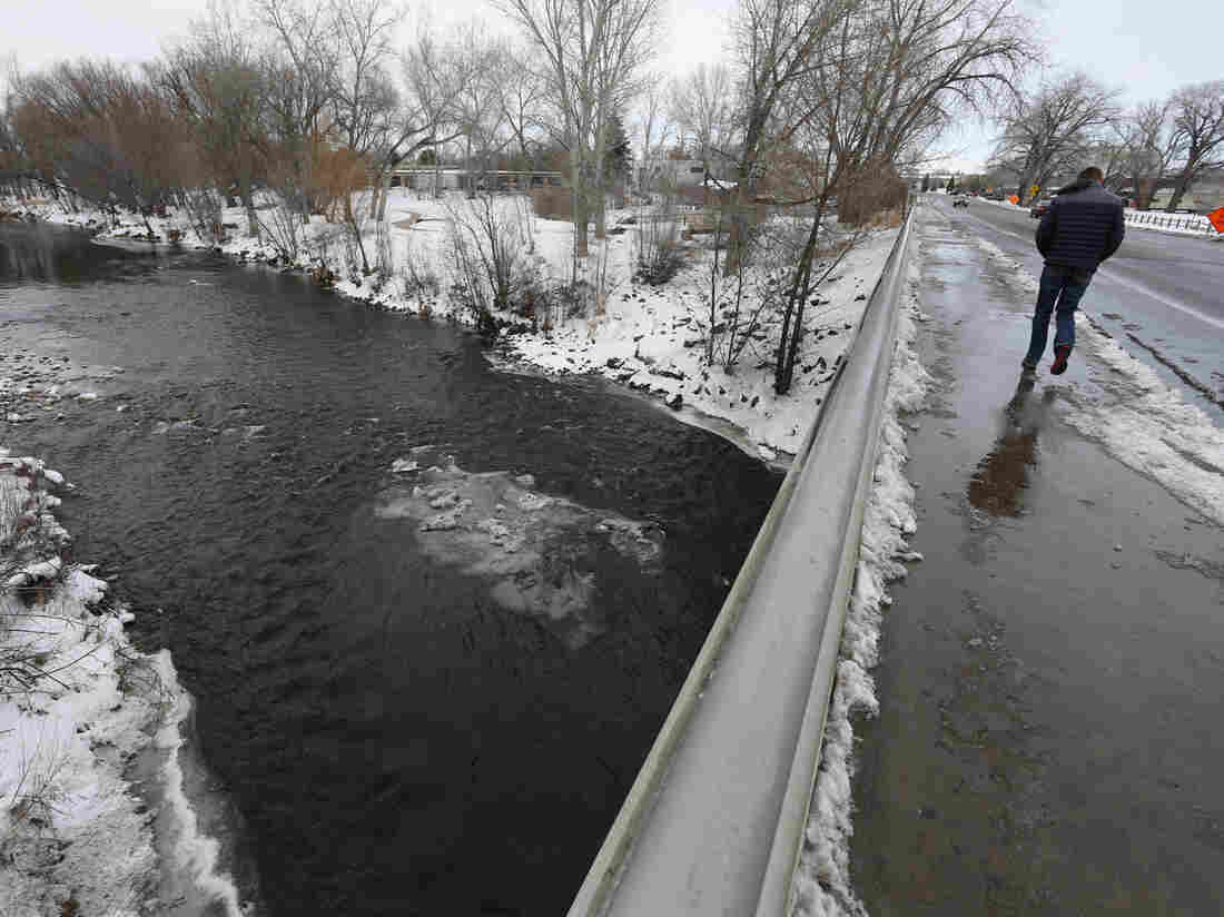 A man crosses a bridge over the Poudre River, in Fort Collins, Colo. The picturesque Colorado river is the latest prize in the West's water wars, where wilderness advocates usually line up against urban and industrial development.