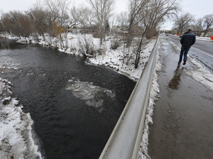 A man crosses a bridge over the Poudre River, in Fort Collins, Colo. The picturesque river is the latest prize in the West's water wars, where wilderness advocates usually line up against urban and industrial development.