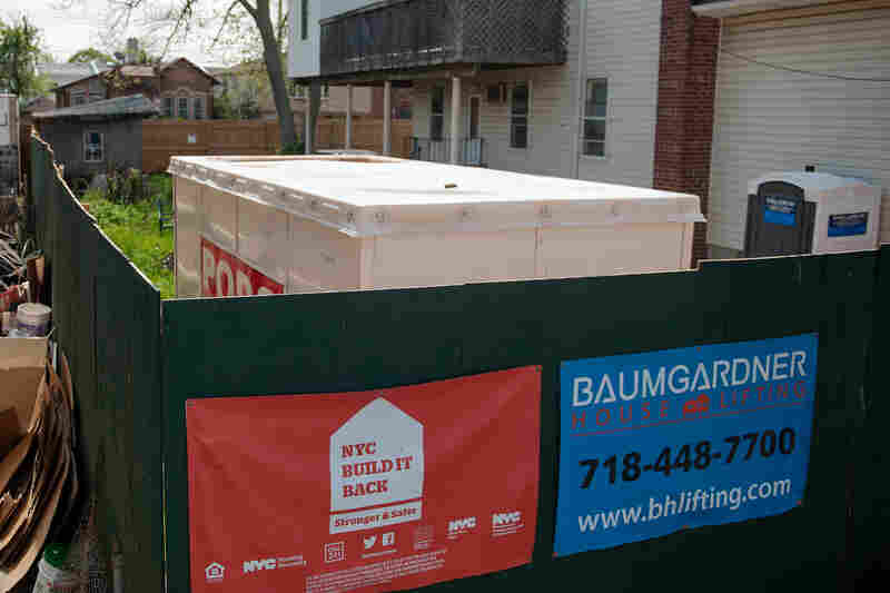 A sign for the Build It Back program hangs on the plywood fence of a construction site on Staten Island, N.Y.