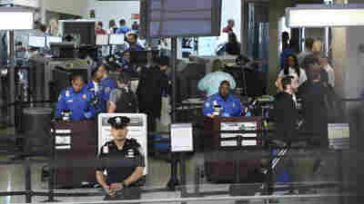 TSA agents work at a security checkpoint at Newark airport in New Jersey on Monday. The House committee says the head of security for TSA has been removed from office after inquiries into the agency's management.