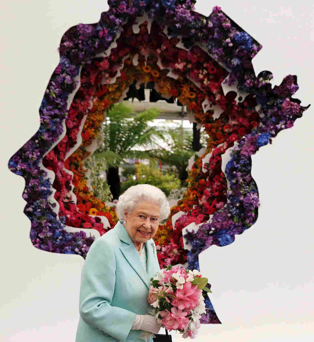 Queen Elizabeth II is pictured beside a floral exhibit at the Chelsea Flower Show that features her own image.