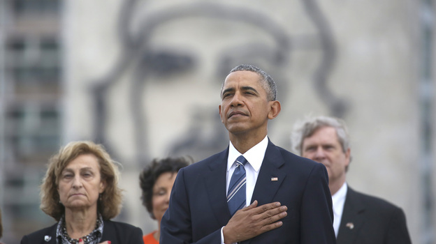 """President Obama listens to the U.S. national anthem in Havana, Cuba, on March 21. Behind him is an image of Cuba's revolutionary hero Ernesto """"Che"""" Guevara. (AP)"""