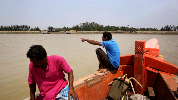 A boat approaches Ghoramara island in India's Sundarbans. Most traffic goes the other way, as thousands of Ghoramara residents have left the flood-prone island in recent years. (NPR)