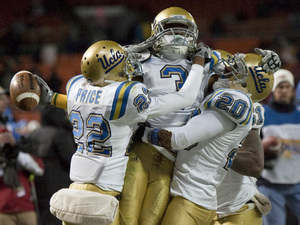 UCLA safety Rahim Moore (center) celebrates an interception against Temple with teammates Sheldon Price (left) and Glenn Love during the third quarter of the EagleBank Bowl in 2009.