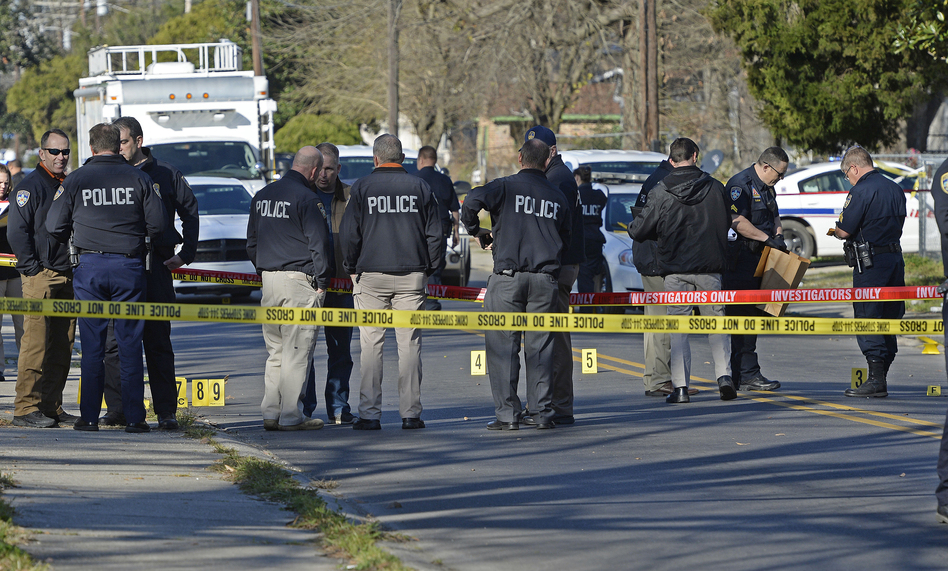 Officers investigate the scene of a shooting in Baton Rouge, La., in February. (Bill Feig/AP)