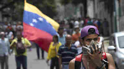 A protester wears a respirator mask during a demonstration against President Nicolas Maduro in Caracas on May 18. Police used teargas against some demonstrators.