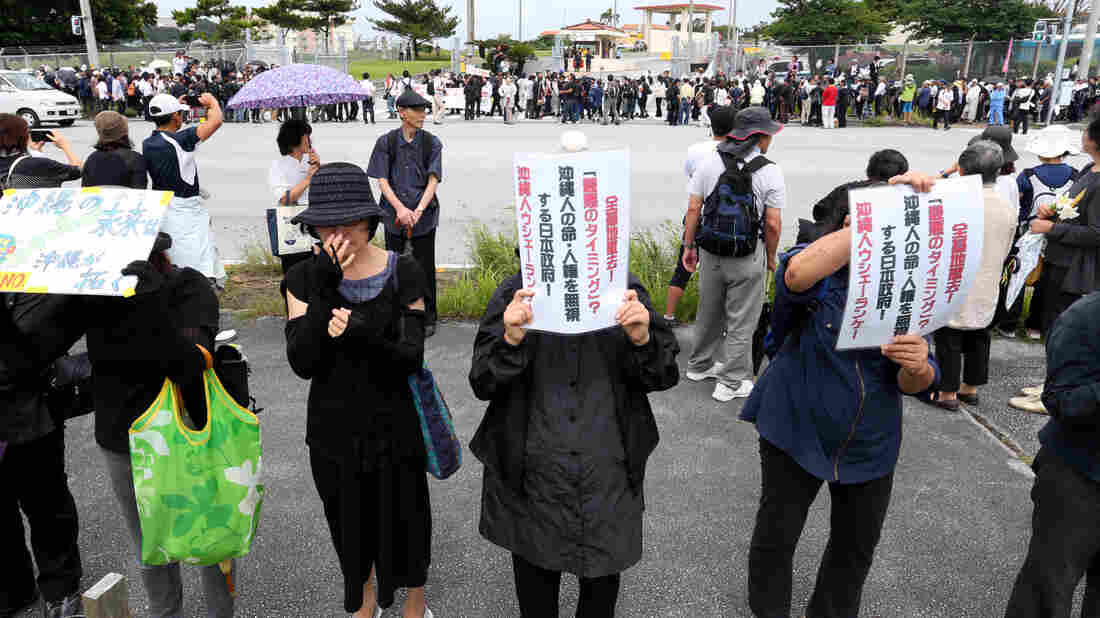 Demonstrators gather in a silent rally to mourn the death of an Okinawa woman in front of Camp Zukeran on May 22. The crime is thrusting the opposition to the U.S. presence on Okinawa back in the spotlight.