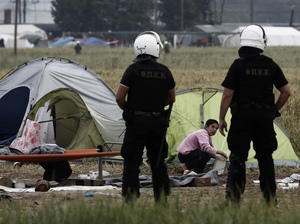 Police officers patrol among tents during evacuation operations Tuesday at the Idomeni camp near the Greek-Macedonian border.