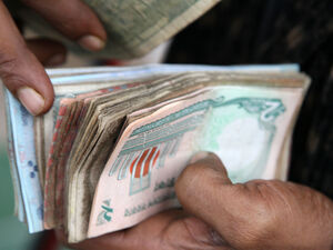 A vendor counts bank notes at a market in Dhaka, Bangladesh.