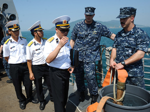 Vietnamese navy officers (in white) talk with U.S. sailors aboard the guided missile destroyer USS Chafee in the central city of Vietnamese of Danang in 2012. The two countries have increased military cooperation in recent years and President Obama announced Monday that he was lifting the ban on weapons sales to Vietnam.