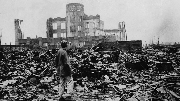 One month after the atomic bomb was dropped on Hiroshima, a correspondent stands amid ruins left by the explosion. The structure seen standing became the Hiroshima Peace Memorial, which President Obama will visit Friday. (AP)