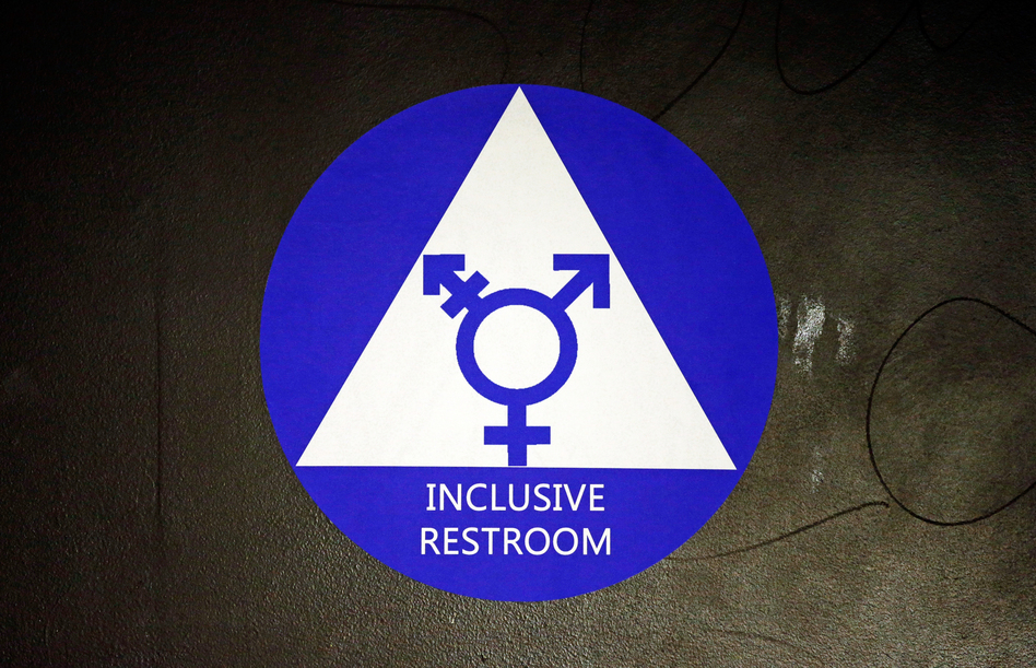 A new sticker designates a gender neutral bathroom at a high school in Seattle. President Obama's directive ordering schools to accommodate transgender students has been controversial in some places, leading 11 states to file a lawsuit against the Obama administration in response. (Elaine Thompson/AP)