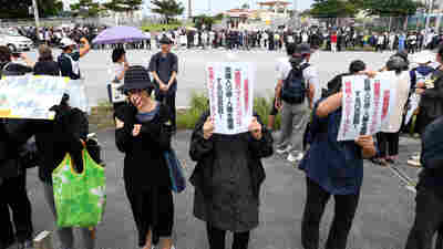 Demonstrators gather in a silent rally to mourn the death of an Okinawa woman in front of Camp Zukeran on May 22. The crime is thrusting the opposition to the U.S. presence on the island back in the spotlight.