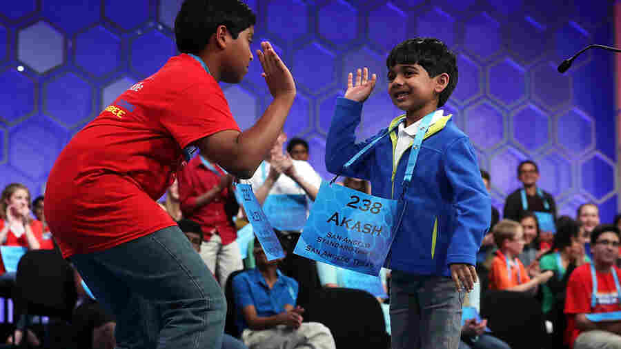 Thirteen-year-old Alex Iyer (left) gives 6-year-old Akash Vukoti a high-five as Akash leaves the stage after misspelling a word in Round 3 of the 2016 Scripps National Spelling Bee on Wednesday in National Harbor, Md.