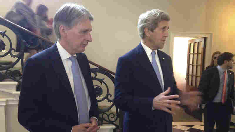 U.S. Secretary of State John Kerry (right), along with British Foreign Secretary Philip Hammond (left), speak to reporters in London on May 12. They tried to assure European banks they won't be penalized for conducting legitimate business with Iran. Critics say it should not be up to the U.S. to encourage investment in Iran.