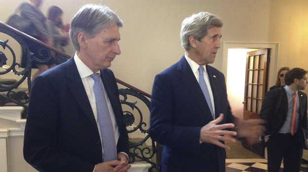 U.S. Secretary of State John Kerry (right), along with British Foreign Secretary Philip Hammond (left), speak to reporters in London on May 12. They tried to assure European banks they won't be penalized for conducting legitimate business with Iran. Critics say it should not be up to the U.S. to encourage investment in Iran. (AP)